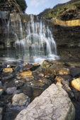 Beautiful landscape image waterfall flowing into rocks on beach  — Stock Photo