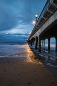 Twilight dusk landscape of pier stretching out into sea with moo — Stock Photo