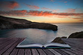 Book concept Beautiful vibrant sunrise over rocky coastline — Stock Photo