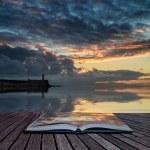 Book concept Beautiful vibrant sunrise sky over calm water ocean — Stock Photo #46622563