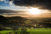 Stunning Summer sunset across countryside landscape with dramati — Stock Photo