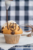 Icing frosting being put onto home made chocolate chip muffins — Stock Photo