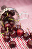 Glass storage jar full of fresh cherries — Stock Photo