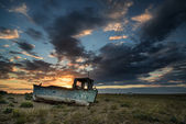 Abandoned fishing boat on beach landscape at sunset — Stock Photo
