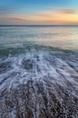 Stunning long exposure seascape image of calm ocean at sunset — Stock Photo
