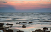 Summer landscape with rocks on beach during late evening and low — Stock Photo