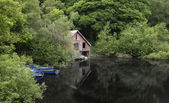 Derelict old retro boathouse and rowing boats hidden in forest l — Stock Photo