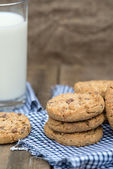 Rustic setting with chocolate chip cookies and glass of milk — Stock Photo