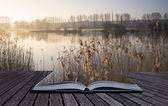 Book concept Landscape of lake in mist with sun glow at sunrise — Stock Photo