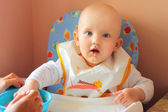 The baby eats porridge — Stock Photo