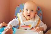 The baby eats porridge — Stock Photo