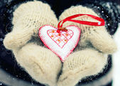 Hands in gloves with decorative fabric heart — Stock Photo