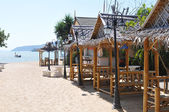 Sunny beach with summer houses — Stock Photo