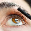 Applying mascara on her eyelashes — Stockfoto