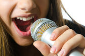 Close up of a girl using a microphone, isolated on a white background. — Stock Photo