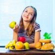 Healthy Food. Beautiful Young Woman choosing between Fruits and Sweets — Stock Photo #34606335