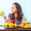 Healthy Food. Beautiful Young Woman choosing between Fruits and Sweets — Stock Photo #34606337