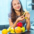 Healthy Food. Beautiful Young Woman choosing between Fruits and Sweets — Stock Photo #34606543
