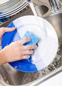 Uzavřete ruce ženy, mytí nádobí v kuchyni — Stock fotografie