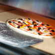 Putting pizza in oven at restaurant kitchen — Stock Photo