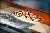 Pizza setzen im ofen bei restaurantküche — Stockfoto