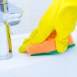 Woman doing chores in bathroom at home, cleaning sink and faucet with spray detergent — Stock Photo