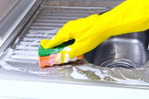 Person cleaning the kitchen sink with a glove — Стоковое фото