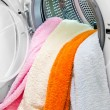 Woman taking color clothes from washing machine — Stock Photo