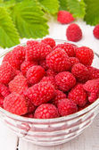Raspberries in a bowl on a wooden table. — Stock Photo
