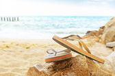 Flip flops on a sandy ocean beach — Stock Photo