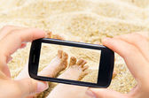 Hands taking photo girl legs in sea with smartphone — Stok fotoğraf