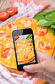 Hands taking photo pizza with smartphone — Stock Photo