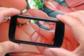 Hands taking photo car interior with smartphone — Stock Photo