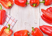 Red peppers on white wooden table. Frame. — Stock Photo