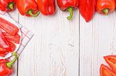 Czerwone papryki na biały drewniany stół. rama. — Zdjęcie stockowe