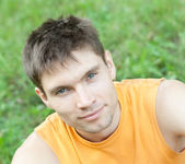 Face portrait of man sitting on a grass — Stock Photo