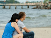 Loving young couple is sitting near the sea — Stock Photo
