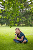 Funny happy girl is sitting on a grass — Stock Photo