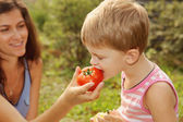 Woman feeds her son vegetables — Stock Photo