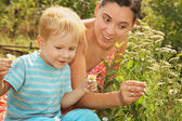 Woman with little son admires daisies — Stock Photo