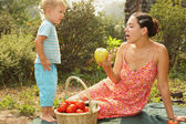 Woman offers little boy apple — Stock Photo