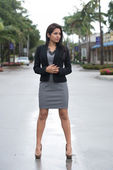 Pretty woman in black jacket and gray dress. — Stock Photo