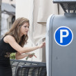Woman putting money in a parking meter — Stock Photo #28415899