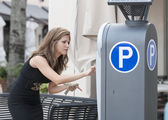 Woman putting money in a parking meter — Stock Photo