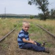Cute little blond boy sitting on railway — Stock Photo