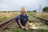 Mignon petit garçon blond jouant sur le chemin de fer — Photo