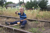 Blond little boy sitting on railway and eating lunch — Stock Photo