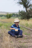 Cute little boy in summer hat sitting on railway and eating lunc — Stock Photo