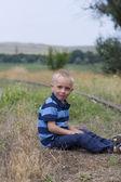 симпатичные блондинка мальчик, сидя на железной дороге — Стоковое фото