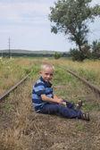Cute little blond boy sitting on railway — Stock Photo